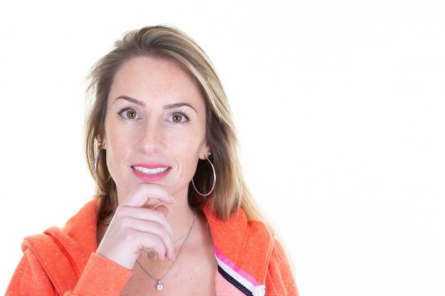 Портрет молодой 35-летней женщины с длинными светлыми волосами, одетой в оранжевый повседневный спортивный свитер