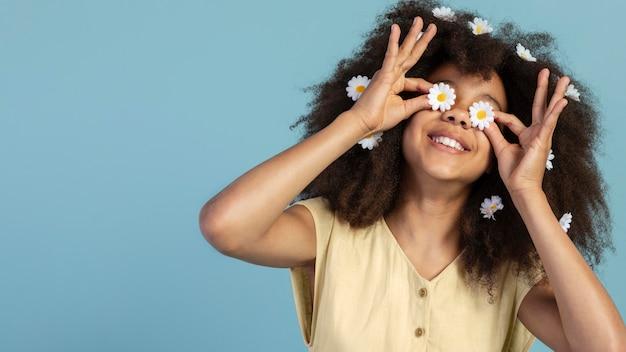카모마일 꽃과 함께 포즈를 취하는 젊은 사랑스러운 소녀의 초상화
