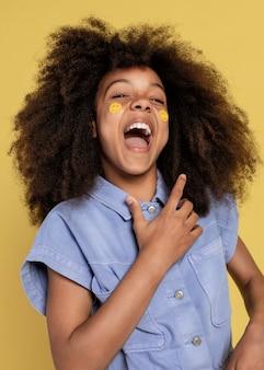 Портрет молодой очаровательной девушки позирует с наклейками смайликов на ее лице
