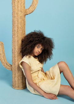 Портрет молодой очаровательной девушки позирует с поддельным кактусом
