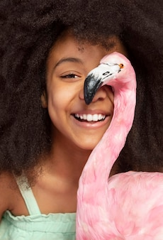 Портрет молодой очаровательной девушки позирует с игрушечным фламинго