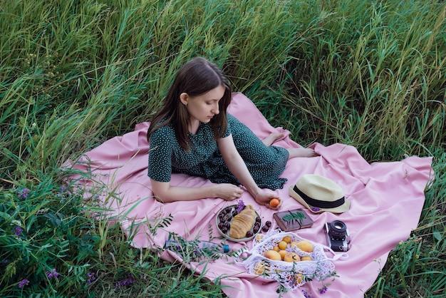 Портрет молодой взрослой женщины в зеленом платье, лежащей на розовом одеяле с фруктами, печеньем и шляпой на открытом воздухе