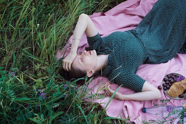 Портрет молодой взрослой женщины в зеленом платье, лежащей на розовом одеяле с фруктами, выпечкой и на открытом воздухе