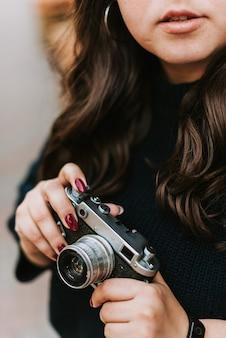 Портрет молодой взрослой девушки, держащей старинный фотоаппарат на открытом воздухе