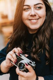 屋外でビンテージカメラを保持している若い大人の女の子の肖像画
