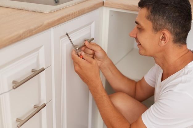 Портрет молодой взрослый красивый рабочий устанавливает новую ручку на белый шкаф с отверткой, выражая положительные эмоции, муж ремонтирует кухонный гарнитур дома.