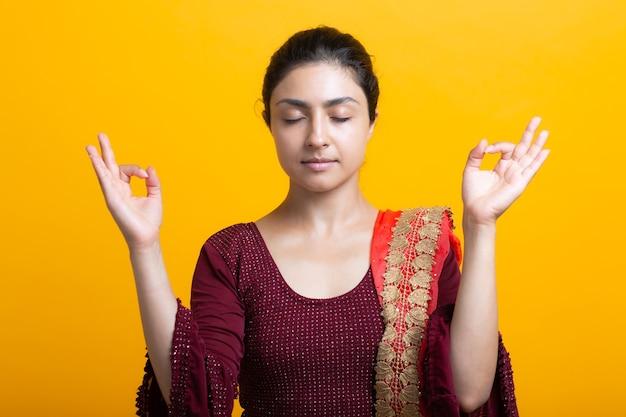 Портрет молодой взрослой индийской женщины в сари медитировать дзен, как с жестом мудры знака ок