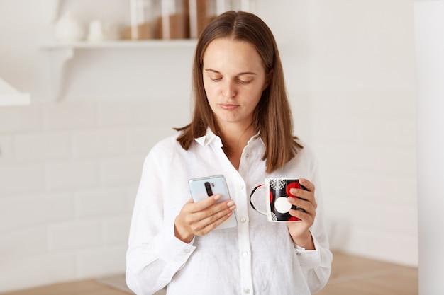 スマートフォンを手に立って、キッチンでコーヒーやお茶を飲み、メッセージを読みながら否定的な感情を表現する若い大人の不幸な女性の肖像画。