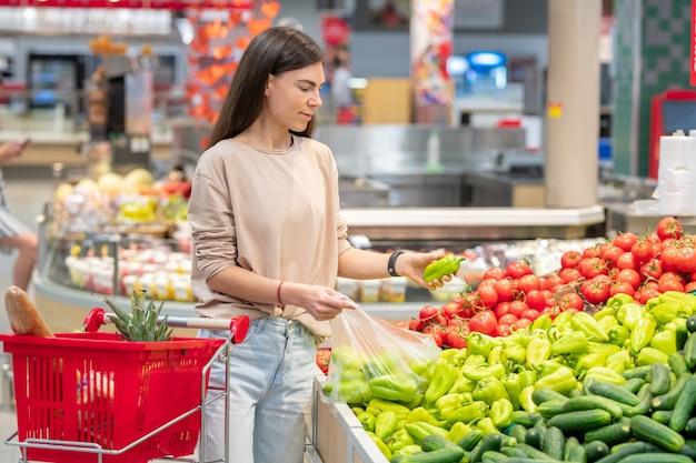 ピーマンを選択してショッピングカートでスーパーマーケットに立っている若い大人の女性の肖像画