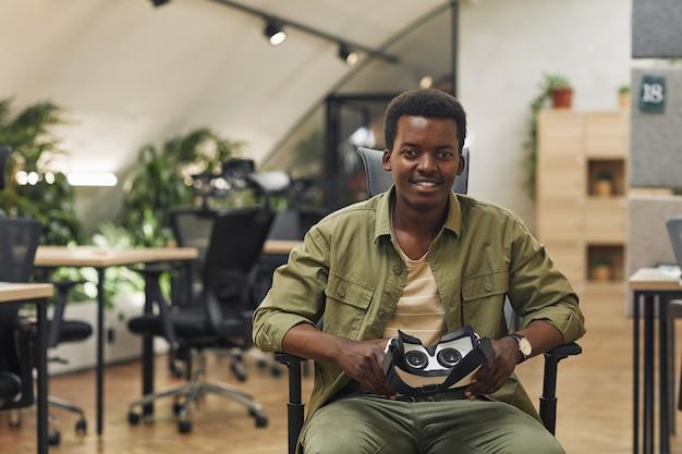Портрет молодого афро-американского мужчины, держащего снаряжение vr и улыбающегося в камеру, сидя в современном офисе, копией пространства