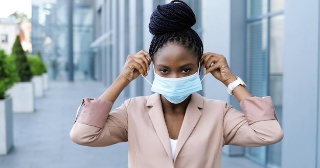 ピンクのジャケットを着た若いアフリカ系アメリカ人の美しい女性の肖像画は、医療マスクを脱いで、屋外のカメラに微笑んでいます。検疫のビジネスセンターの近くの通りで魅力的な陽気な実業家。