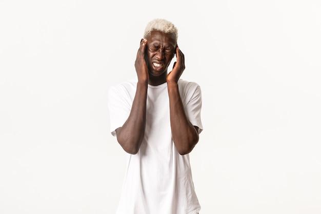Портрет молодого афроамериканского блондина с сильной головной болью, касающимся головы и гримасой от боли, страдающим мигренью