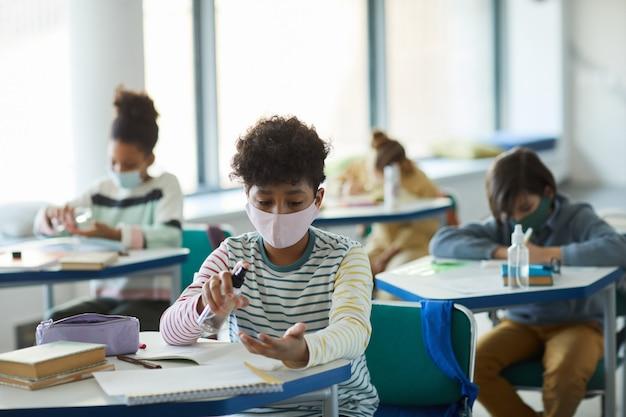 학교 교실에서 손을 소독하는 아프리카계 미국인 소년의 초상화, 코비드 안전 조치, 복사 공간