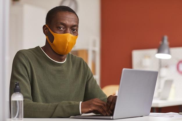 마스크를 착용하고 사무실 칸막이에서 작업하는 동안 노트북을 사용하는 젊은 아프리카 계 미국인 사업가의 초상화, 복사 공간