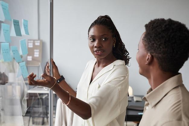 オフィス、コピースペースのガラスの壁のそばに立って一緒にプロジェクトを計画しながら男性の同僚と話している若いアフリカ系アメリカ人実業家の肖像画