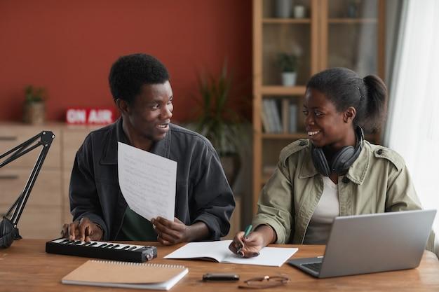 젊은 아프리카 계 미국인 부부의 초상화 함께 음악을 작곡하고 서로 행복하게 웃고보고
