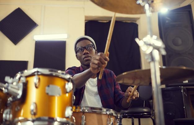 Портрет молодого афро-американского барабанщика, готовящегося к концерту или репетиции во время проверки звука