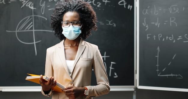 Портрет молодой афро-американской учительницы в очках и медицинской маске, глядя на камеру в classrom и держа тетради. доска с формулами на фоне. пандемия школьного образования.