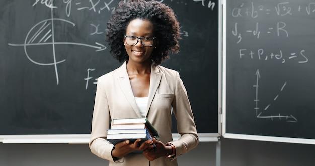 Портрет молодой афро-американской учительницы в очках, глядя на камеру в classrom и держа учебники. доска с формулами на фоне. концепция школьного обучения. книги в руках женщины.