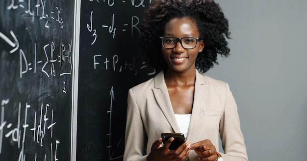 Портрет молодой афро-американской учительницы в очках, улыбаясь в камеру в классе и держа смартфон. доска с формулами на фоне. концепция школьного обучения. женщина с мобильным телефоном.