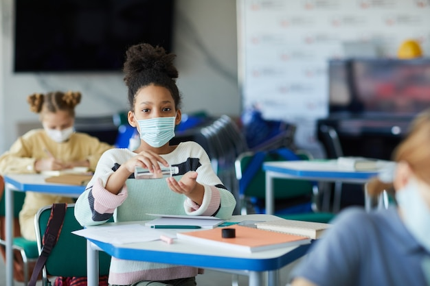 학교 교실에서 손을 소독하는 젊은 아프리카계 미국인 소녀의 초상화, 코비드 안전 조치, 복사 공간