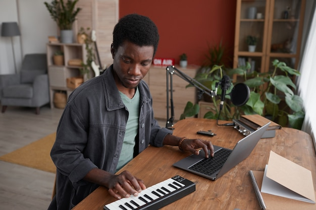홈 녹음 스튜디오에서 음악을 작곡하는 젊은 아프리카 계 미국인 남자의 초상화, 복사 공간