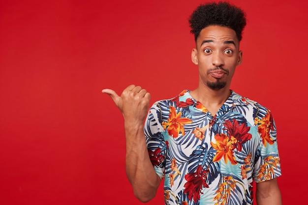 アロハシャツを着た若いアフリカ系アメリカ人男性の肖像画は、驚いて幸せそうに見え、赤い背景の上に立って、コピースペースで左を指しています。