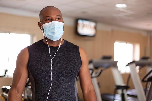 운동복을 입은 젊은 흑인 남자의 초상화. 그는 체육관에 있으며 감염을 피하기 위한 예방 조치로 의료 마스크를 착용하고 있습니다.