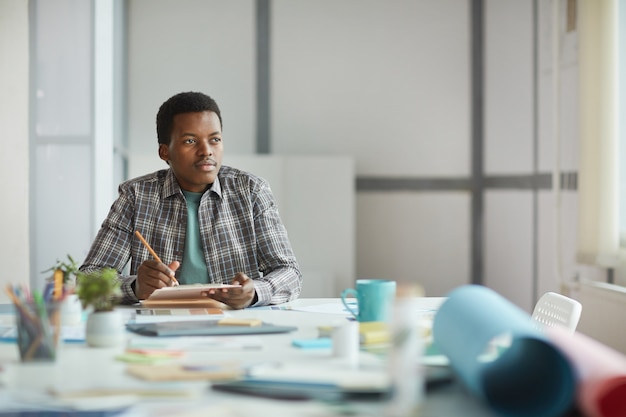 オフィスのメモ帳、コピースペースに創造的なアイデアを書きながら、しんみりと目をそらしている若いアフリカ系アメリカ人の男の肖像