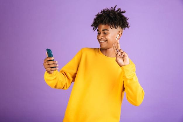 笑顔とスマートフォンでselfieを取り、bluetoothイヤポッドを身に着けて、紫色の背景で隔離の若いアフリカ系アメリカ人男性の肖像画
