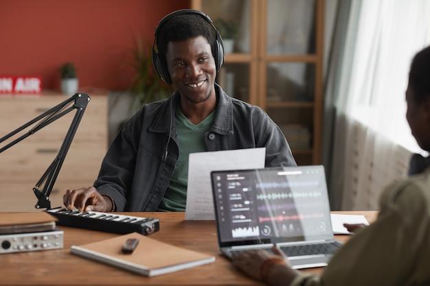 파트너와 함께 집에서 음악을 작곡하는 동안 행복하게 웃고있는 젊은 아프리카 계 미국인 남자의 초상화