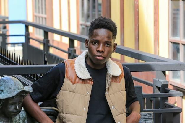 Портрет молодого афро-американского человека, окрашивающего на открытом воздухе.