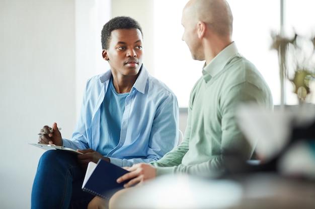 オフィスでのビジネスインターンシップ中にマネージャーと話している若いアフリカ系アメリカ人男性の肖像画、コピースペース