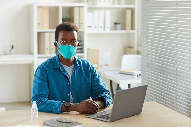 Портрет молодого афро-американского человека в маске, работающего за столом в офисе после пандемии