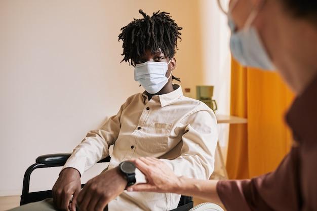 병원에서 치료사와 상담하는 동안 마스크를 쓴 젊은 아프리카계 미국인 남자의 초상화 프리미엄 사진