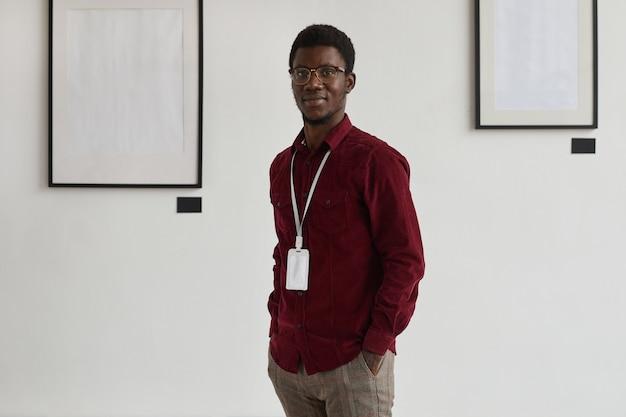 아트 갤러리 또는 전시회에서 작업하는 동안 주머니에 손을 가진 젊은 아프리카 계 미국인 남자의 초상화,