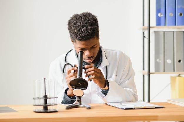 연구를 위해 테스트 샘플을 준비하는 실험실에서 일하는 젊은 아프리카 계 미국인 남자의 초상화, 복사 공간
