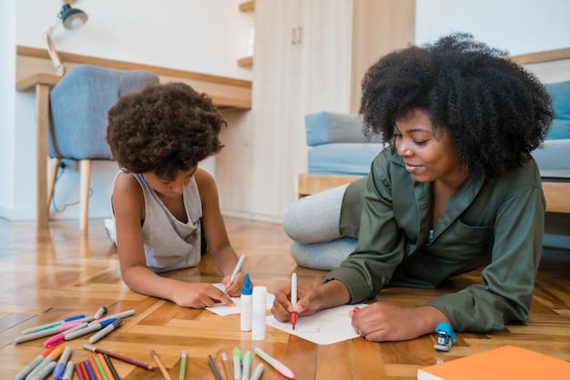 Портрет молодой афро-американской матери и сына, рисунок цветными карандашами на теплом полу дома. семейное понятие.