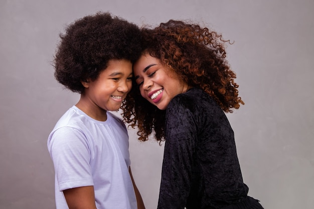幼児の息子と若いアフリカ系アメリカ人の母親の肖像画。灰色の背景。ブラジルの家族。