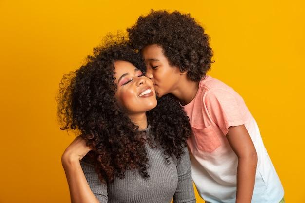 幼児の息子を持つ若いアフリカ系アメリカ人の母の肖像画。息子が母親にキスします。黄色の壁。ブラジルの家族。