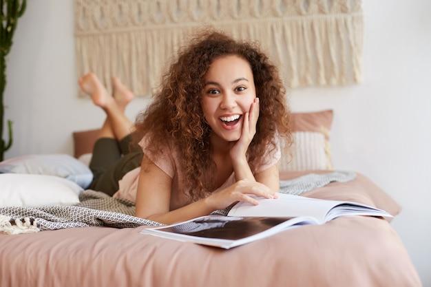 Портрет молодой афро-американской удивленной женщины с вьющимися волосами, лежит на кровати и читает новый журнал, касается щеки, широко улыбается и наслаждается крутыми новостями в журнале, проводит свободное время дома.