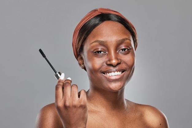 Портрет молодой афро-американской женщины, наносящей макияж на сером фоне и держащей палочку для туши, изолированную вырезом
