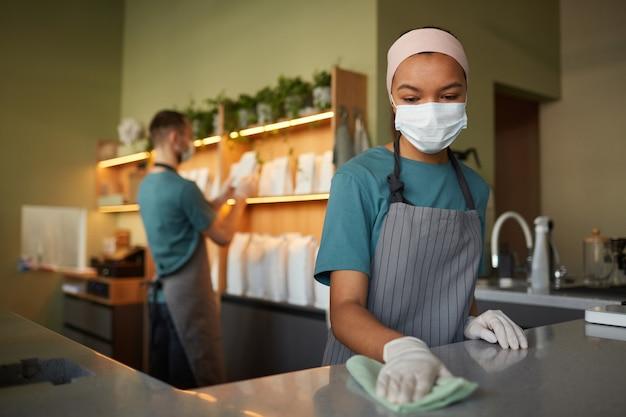 カフェやコーヒーショップで働いている間、消毒剤でバーカウンターを掃除している若いアフリカ系アメリカ人女性の肖像画、安全対策、コピースペース