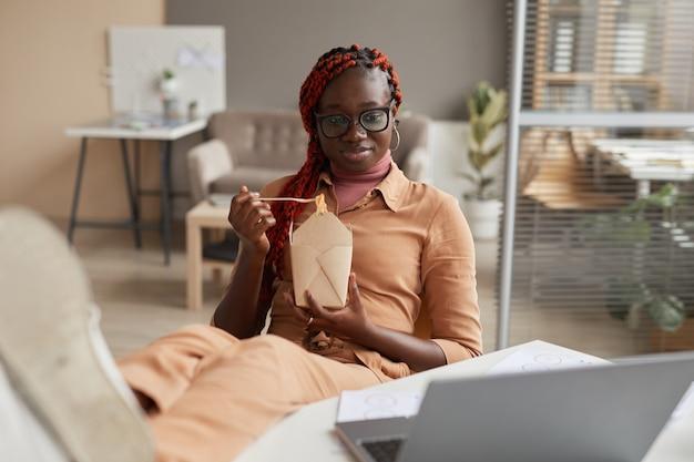 테이크 아웃 음식을 먹고 집 사무실에서 휴식하는 동안 노트북 화면을보고 젊은 아프리카 계 미국인 여자의 초상화, 복사 공간