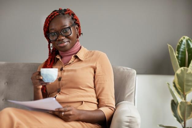 コーヒーマグカップを持って、ホームオフィス、コピースペースからの仕事を楽しみながらカメラに笑顔の若いアフリカ系アメリカ人女性の肖像画