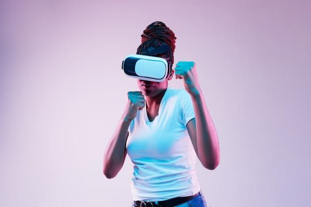 グラデーションのネオン光のvrメガネで遊んでいる若いアフリカ系アメリカ人女性の肖像画。