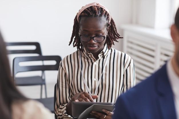 Портрет молодой афро-американской женщины, делающей заметки на цифровом планшете, сидя в аудитории на бизнес-конференции, копией пространства