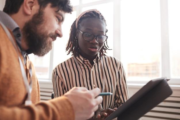 Портрет молодой афро-американской женщины разговаривает с коллегой и смотрит на планшет во время обсуждения бизнес-проекта в офисе