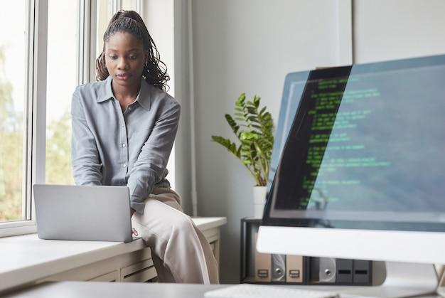 Портрет молодой афро-американской женщины, использующей ноутбук, сидя у окна в офисе разработки программного обеспечения, кодовый экран на переднем плане, копировальное пространство