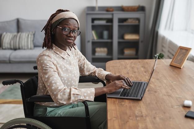 車椅子を使用し、最小限の灰色のインテリア、コピースペースで自宅で仕事をしながらカメラを見ている若いアフリカ系アメリカ人女性の肖像画